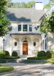 Designed by William T. Baker, a noted residential designer, the home takes its cues from English Regency architecture. In lieu of a front porch, Baker suggested intricate ironwork for a stunning point of entry.
