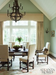 Sage green walls in the dining room offer the biggest dose of color. To complement the architecture, interior designer Joy McLean selected an antique-inspired table and chairs from Holland & Company. The rug is from Patrick James Inc.