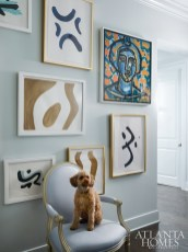 A gallery wall by the entryway includes a portrait by America Martin and abstracts by Brian Carter.