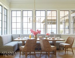 As a young and active family, the couple frequently host friends and family members, so Howard designed spaces—such as this large breakfast room—to accommodate impromptu gatherings. The custom banquette features a graphic F. Schumacher fabric, while chairs from Palecek add nautical charm, an appropriate touch given the room's view of the river. Table, Tritter Feefer. Chandelier, Arteriors.