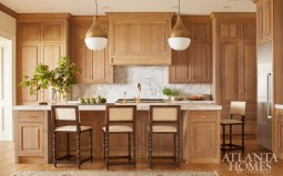 """""""This was a try-something-new moment where we stepped out of the box,"""" says Howard in reference to the kitchen's bleached-oak cabinetry. Knowing today's popular all-white kitchen would feel out of place in this home, his design relied on creating a space infused with warmth. He used traditional-style barstools from the family's former home and selected new metal Eccola light pendants overhead for contrast."""