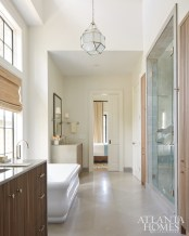 The master bath's clean-lined design features limestone flooring and waterfall-edge vanities. Tall windows allow for an abundance of natural light, even when the shades on the lower portion are drawn for privacy. The soaking tub is from Ferguson.