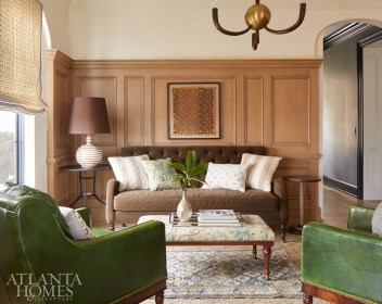The Woodall's existing green leather chairs add a pop of color in the cozy family room. Newer items include a roman shade crafted from a Martyn Lawrence Bullard fabric and a framed kuba cloth tapestry.