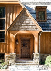 A cedar-shake roof, cypress board-and-batten siding and stacked stones make this home—designed by architect Greg Busch and interior designer Meridy King—look in harmony with the wooded landscape.