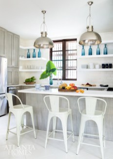 Custom limewashed cabinets paiir with Caesarstone countertops, Company pendants and open shelving for beach-chic appeal.