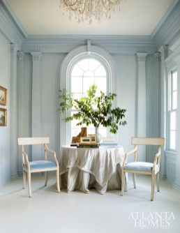A glacier-hued Brunschwig & Fils velvet on Niermann Weeks chairs complements the icy blue hue on the walls of the side entry foyer. Skirted table fabric, J. Robert Scott and Fret.