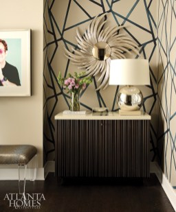 Wallpaper by Harlequin, sourced from Grizzel & Mann at ADAC, gives graphic interest to the entryway, which includes an Elton John image by Joseph Guay.