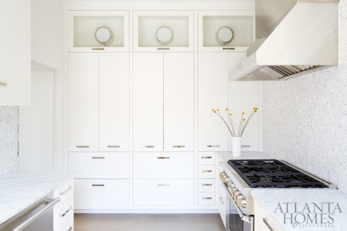 """It took quite a while to lay out the kitchen because it was such a small space,"" says Kay, who worked with Tupper Construction to wrap the room almost entirely in cabinets. To add light without disturbing the ceiling beams, the team installed flush-mount fixtures on the wall in the upper parts of the cabinets. The backsplash tiles are the same gray-veined Carrara marble used for the countertops."