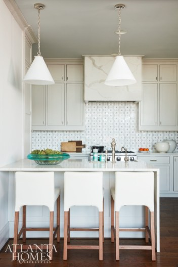 The petite kitchen is big on style with a custom tiled New Ravenna backsplash in a flower pattern. Pendants, Visual Comfort.