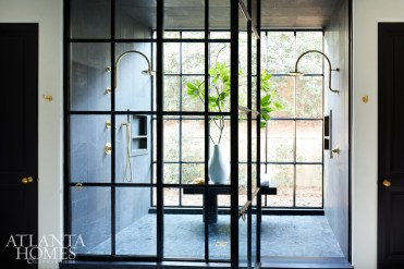 """Perhaps one of the home's most intriguing elements is the master bath's shower, which features custom doors and a window that faces the backyard (there's a retractable screen for privacy). """"We wanted it to feel like you were outside at all times, so we did an outside shower window that looks into your garden,"""" says Turner."""