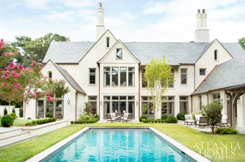 The swimming pool is perhaps best enjoyed on a patio bound by a bank of tall windows, which stands opposite the entryway and provides a sightline from the front door to the idyllic backyard, where landscape architects Hooten Land Design Inc. designed the grounds.