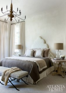 """With the subtle pattern of its custom headboard nearly blending into the soft plaster walls (they have a slightly mottled effect, which adds more depth, Westbrook notes), the quietude of the master bedroom verges on divine. """"I always believe that a bedroom should be a retreat and should be restful,"""" says Westbrook, who layered lots of tactile textures for the bedclothes, including cotton, linen and faux fur. """"The [cove] ceiling is so gorgeous in that room that there's absolutely no reason to hang art over that headboard. The shape itself becomes decorative,"""" she adds. Bedside table, Bungalow Classic."""