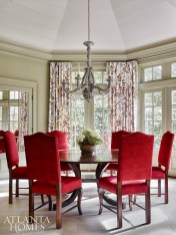 The octagonal dining room reveals rich red chairs from Holland and Co. and a New Classics dining table through Ainsworth-Noah.