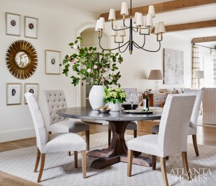 An original sunburst mirror—a family heirloom—is highlighted in the new dining room, where Lauren Davenport Imber selected a round RH table with a metal top. An arrangement by Forage and Flower joins camellias from the garden.