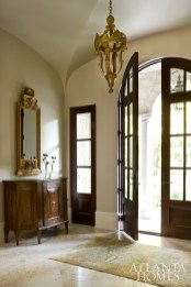 Arched doorways are a common thread sewn throughout the English-inspired home. In the formal entryway, an antique credenza from William Word Fine Antiques and a gold mirror from Provenance Antiques set the stage for the vast yet highly personalized interiors.