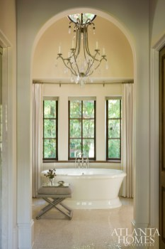 A Dennis & Leen chandelier elevates the serene master bathroom, where a custom Block & Chisel–made vanity resembles an antique piece that masterfully mixes refinement with function.