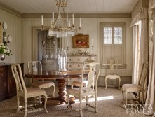 "The homeowner's antique Swedish chandelier established the tone for the dining room. Lanham enlisted artisan Raymond Goins to paint tone-on-tone greige panels, and Litchfield and his associate Tiffany Watkins further articulated the Swedish feel with casings and vertically ribbed cornices. ""We wanted it to be a little jewel box, a bit of a surprise,"" says Lanham."