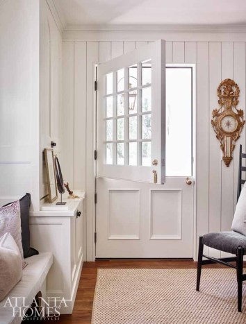 A Dutch door offers a casual entrance from the driveway—via a small sitting porch—into one of the renovated home's two mudrooms. Originally part of the home's kitchen, this space speaks to the modern family's desire to live more casually. The mudroom, which also contains a powder room, opens to the formal dining room as well as to the butler's pantry, kitchen and breakfast nook.