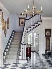 Designed on an axis that leads the eye from the entrance to views of the rear courtyard's infinity-edge pool and beyond, this three-story stairwell was transformed from a dark wood stain to a high-contrast palette thanks to a scroll on the stair skirt board Lanham painted black-and-white and a dynamic floor pattern from Renaissance Tile & Bath.