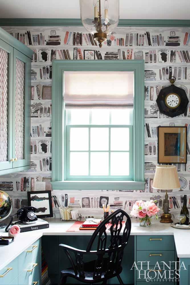 """""""With so much cabinet storage—and a dedicated surface for organization—life also feels civilized and orderly,"""" says Kirkland of this chic office space. Farrow & Ball's Castle Gray anchors the space and sets the tone for a remarkably refined palette that still leaves room for a dose of whimsy in the form of the Kate Spade for Kravet wallpaper artfully alluding to a collection of books in a library."""