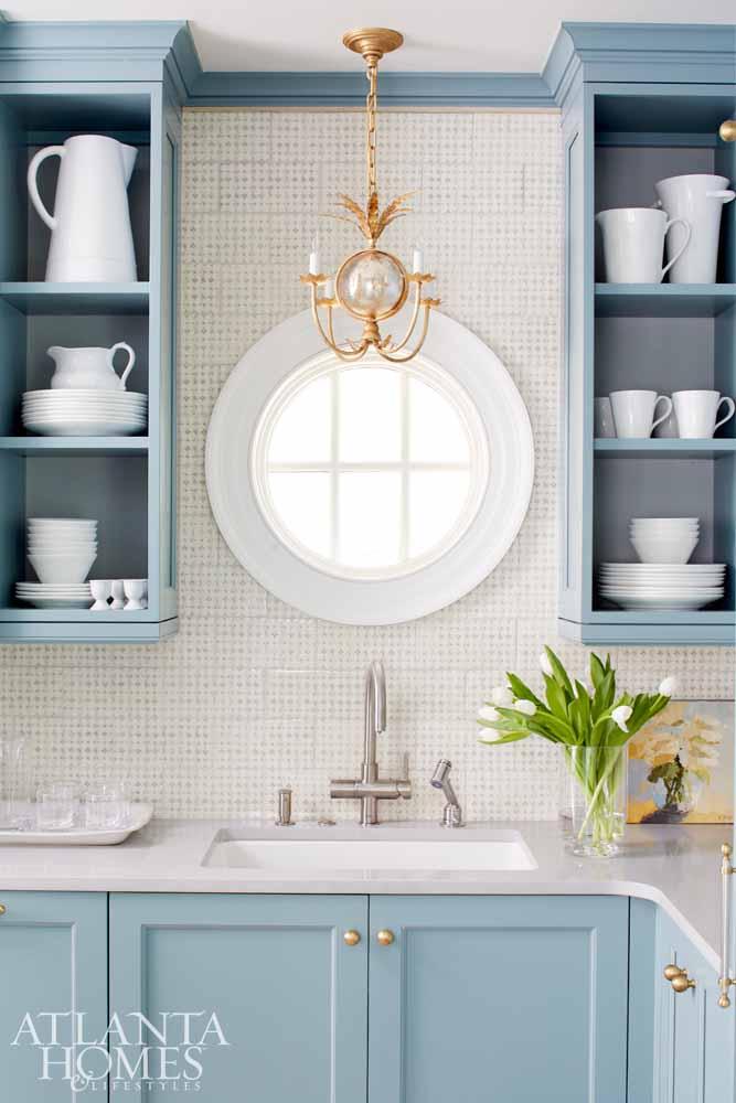Kitchen with light blue cabinets, white marble, kitchen sink, gold chandelier