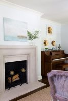 While the living room did not change dramatically in the renovation, it did receive a beautiful limestone fireplace topped by a dreamy painting by Laura Hathaway and striking gilt floral medallions above the piano.