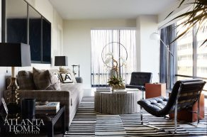 In the living room, an antique black-and-white rug sourced from rug collector Betsy Murphy creates a striking conversation piece, as does an inlaid table from Anthropologie. The sofa was designed by Khandwala through Westside Custom Upholstery. The chairs are vintage by Ingmar Relling for Westnofa. The custom wall painting is by Atlanta artist Todd Seay.