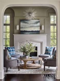 """Jimmy Stanton painted the parlor of this Chastain Park home Benjamin Moore's Briarwood, a striking dark khaki. """"It's light during the day and takes on a beautiful darker glow at night,"""" Stanton says. Artwork by Jill Holland available through Gregg Irby Gallery."""