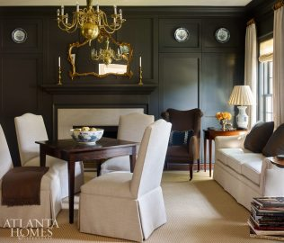 The living room-cum-study is moody but mindful. Collectively, its dark walls, bold brass and symmetrical sightline almost recall the well-mannered glamour of Dorothy Draper's Victorian Writing Room at the Greenbrier Hotel. Even the handsome card table could easily sub as a writing desk.