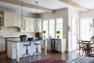 The kitchen is a classic creamy white with glass-front cabinets; beams with a whitewash finish bring another layer of texture.