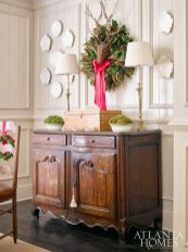 The pinecone-petal deer with twig antlers is perched above the chest year-round; here, a festive wreath by Le Jardin Français creates a focal point.