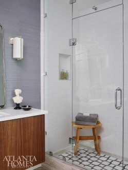 A luxe yet durable vinyl silk wallcovering by Phillip Jeffries is the backdrop for the bathroom's chic accents, including a floating vanity fabricated by Royal Custom Cabinets, a leaning mirror by Rejuvenation and Circa Lighting sconces.