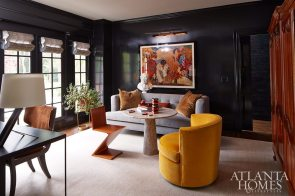 """Black lacquered walls envelop the game room. """"There were three somewhat disparate pieces we needed to incorporate: a painting from New Orleans, a mustard velvet chair and a large armoire made by the wife's grandfather,"""" says van den Bergh. Adds Musso, """"The common thread is they all have a French feel to them."""" A Cassina chair, originally designed by Gerrit Rietveld in the 1930s, adds another bold punctuation point."""