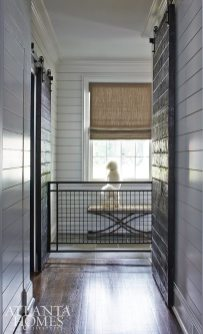Many of the service area's details were designed with Oscar, the family's bichon frise, in mind. Greg DeLoach, the project's contractor, charred barn doors in the mudroom and laundry area with a Japanese method called shou sugi ban to give the wood a deep charcoal appearance and highlight the grain.