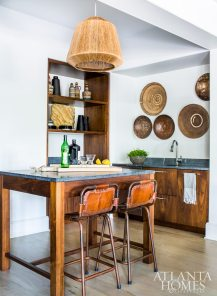 While McFadden wanted the lower level living area to be a bit playful, she also wanted the kitchen's walnut cabinetry to stand out. A pair of aged-leather barstools and a collection of antique baskets add to its textural appeal.