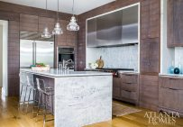 The horizontal, custom-finished white oak plank cabinetry by Morgan Creek Cabinet Company plays a starring role, bringing warmth to the kitchen against the starker natural quartzite with its gray and blue-green tones.