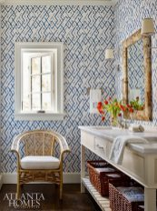 In the nearby guest bath, a graphic Jim Thompson wallcovering adds major impact while birch-bark mirrors and a vintage rattan chair keep the space from feeling too modern.