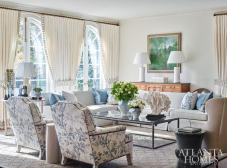 "An outdated Nashville residence saw a dramatic architectural and interior transformation at the hands of local designer Jonathan Savage, who sourced a majority of the fabrics and furnishings in Atlanta. ""I was inspired by a French salon,"" Savage says of the light-filled family room, which features a GP & J Baker floral fabric on tight-back arm chairs; a coffee table repurposed from a gate procured from a property in Rue de Lille, Paris; and linen window treatments adorned with a hand-painted border by Coleman & Taylor Textiles. One of Savage's most dramatic moves was to replace the original transom-topped windows with fully operable French doors built by Vintage Millworks."