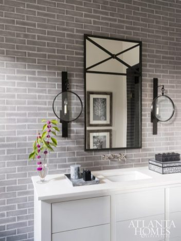 Dark gray subway tile from Ann Sacks adds a masculine feel to this guest bath; the mirror is through Mirror Image Home and the sconces are through Circa Lighting.