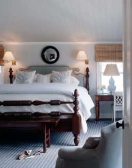 Howard's nuanced blues reveal themselves in a bedroom in which striped wallpaper on the ceiling pairs with a coordinating color on the walls to expand the sense of space.