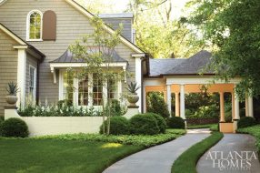 A porte cochère, part of a renovation by architect D. Stanley Dixon, beckons guests to this Buckhead cottage. A grass strip adds an interesting classic detail.
