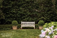 Limestone containers accompany a bench for a sweet spot in the rear courtyard bordered by a hedge of clipped Korean boxwood.