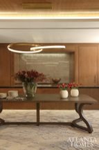 In lieu of a serving counter, a custom Christian Liaigre table adds residential feel. The chandelier is by Christopher Boots via R Hughes; the glass tile is Ann Sacks.