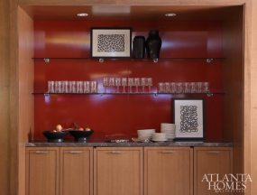 Suzanne Kasler Interiors wanted to remain mindful of the concepts and palettes introduced by the architects into the stadium; the firm employed red lacquer accent walls on both floors of the suite. The marble counter is through Marmi Natural Stone.