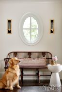 An inherited antique Windsor bench looks fresh with Currey & Company tortoise-and-brass sconces and a contemporary side table from B.D. Jeffries; dog Dallas looks on.