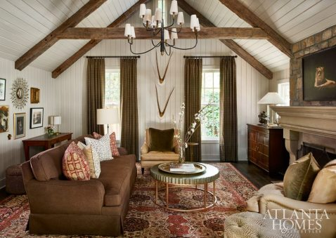 """""""We wanted the family room to be familiar yet stylish and modern at the same time,"""" says Woodbery. The tailored space shows off generous leather upholstery in shades of caramel and brown mixed with olive in the coffee table top and window treatments. """"We also included an animal print and a floral batik in the pillows for a little bit of pizzazz,"""" says Woodbery."""