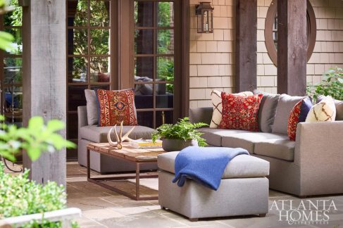 """Woodbery covered a sectional from the couple's former residence in a Perennials fabric to make it suitable for outdoor living. """"I went to a rug dealer and we had old rugs in need of repair made into pillows,"""" she says. """"They play off the rug and window treatment in the billiards room."""""""