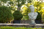 A generously sized bust near the pool house provides a graceful focal point in the garden.
