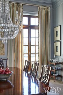 Textures are at play in the formal dining room, which boasts stone floors and boiserie French paneling on the walls, painted Benjamin Moore's Wedgewood Gray.