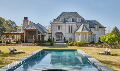 Here, the home's overall Normandy-style architecture is evident. To accommodate the Hughes' vision of a French country home, Pak incorporated classic French windows and doors—sourced from Menuiserie Thareaut in Normandy— into the overall design. Limestone surrounds, a slate roof and stucco exteriors also convey a French-inspired feel. A screened porch and outdoor grill area feature a table and benches that Allen built from black walnut, which was recycled from trees he cut down on the property.